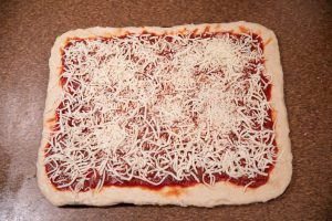 Pizza has sauce and cheese and is ready to go into the oven.