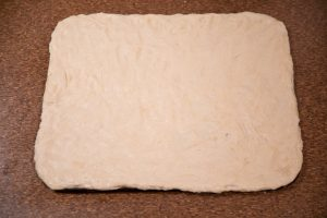 Pizza dough is formed into pizza shape on a pizza stone.