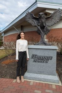 Kayla stands in front of the Prof statue by the Rowan University team house.