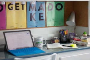 A laptop on a desk with office supplies, with colorful posters in the background.