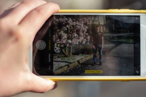 a hand holding a yellow phone case, with the camera app opened on the phone