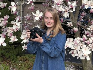 Nicole stands in front of a magnolia tree with a camera.