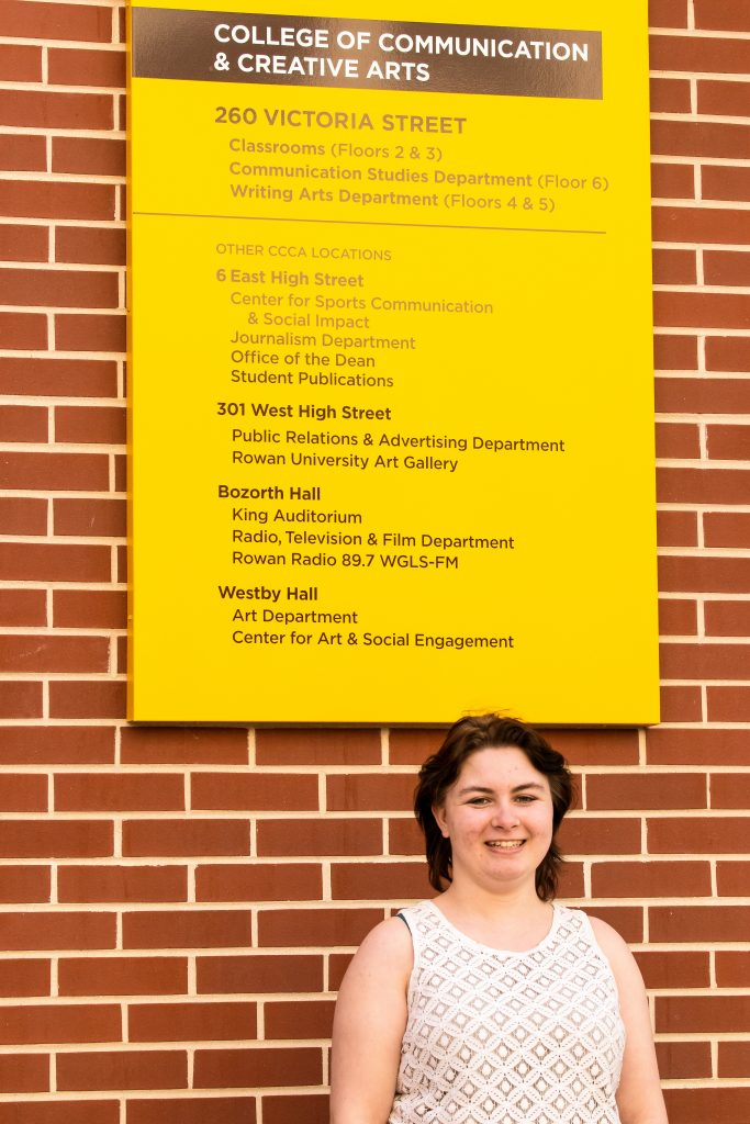 Marissa stands below a sign for the communications building.