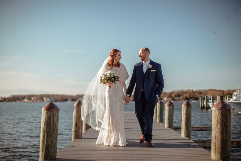 Enchanted Celebrations photo of bride and groom holding hands on a dock with water behind them.