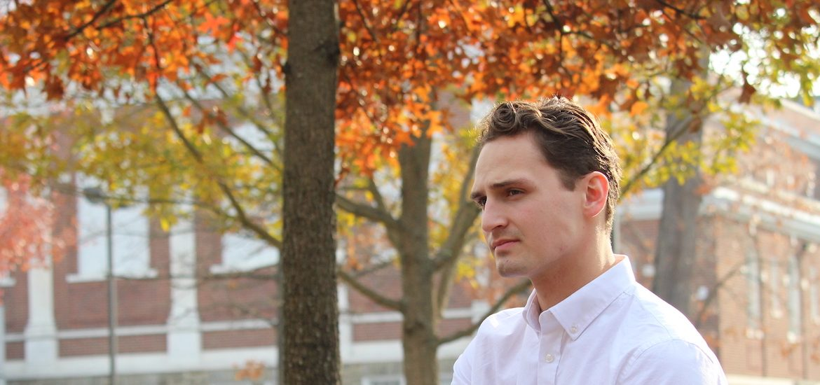 Adam looks into the distance, while wearing a crisp white button down shirt and fall colored trees behind him.