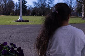 Girl stares into the distance as we see the back of her head and ponytail.