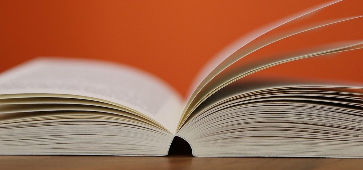 Stock image of an open book fanned against an orange background.