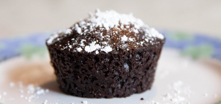 A chocolate cupcake with powdered sugar on top on a plate.