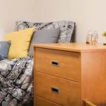dorm room with gray comforter on bed and wooden desk and drawers.