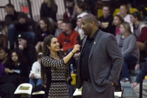 Kayla holds a microphone up for basketball coach Demetrius Poles during a sideline interview.