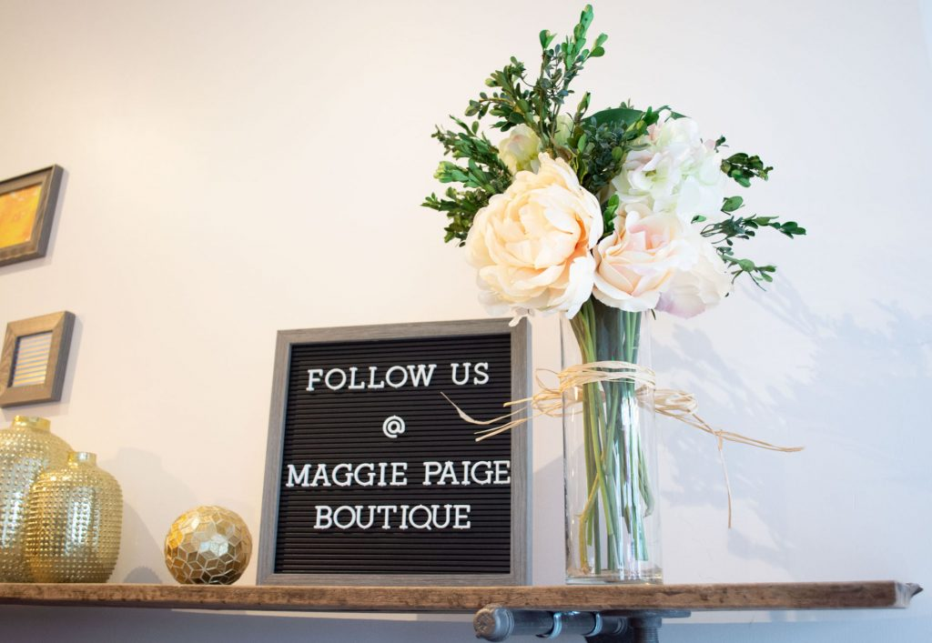 Interior shot of Maggie Paige Boutique with social media link