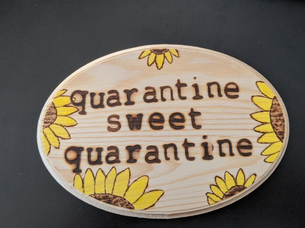 "An oval piece of craft wood with painted sunflowers and woodburning message ""Quarantine Sweet Quarantine."""