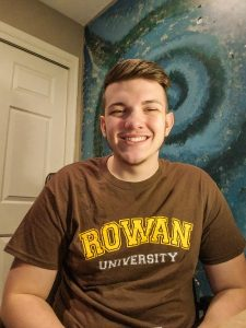 Doug smiles at home wearing a brown Rowan t-shirt.