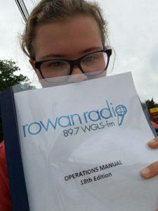 Amanda, wearing glasses, holds up the Rowan Radio Operations Manual