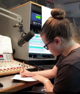 Amanda writes at a desk with a microphone and audio mixing equipment at the Rowan radio station.