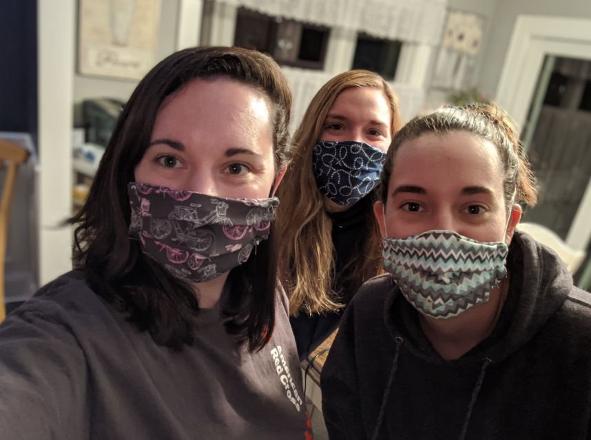 Brittney and her two sisters stand with mouths covered by homemade masks.
