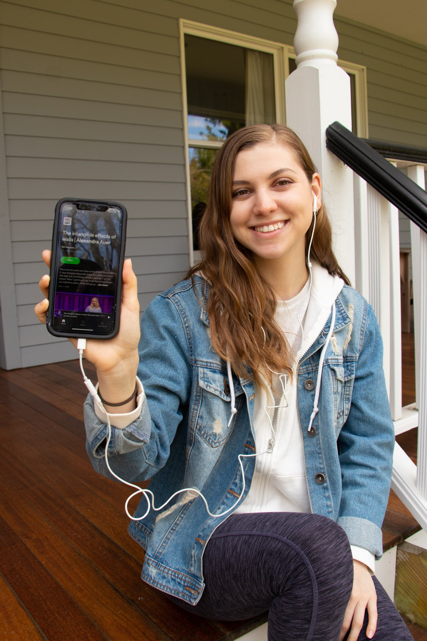 Alyssa Bauer sits on a porch listening to a podcast.