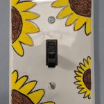 A white light switch painted with sunflowers.