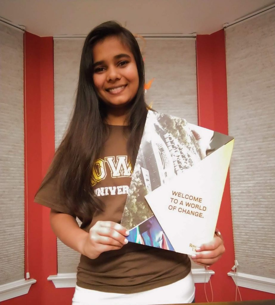Aarushi wears a brown Rowan t-shirt and holds up her admissions package.