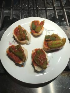 Peppers and tomato on slices of bread.