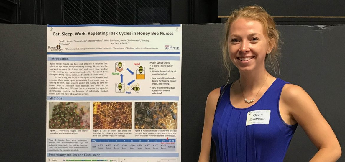 Olivia stands in a blue tank top next to a poster during a presentation.
