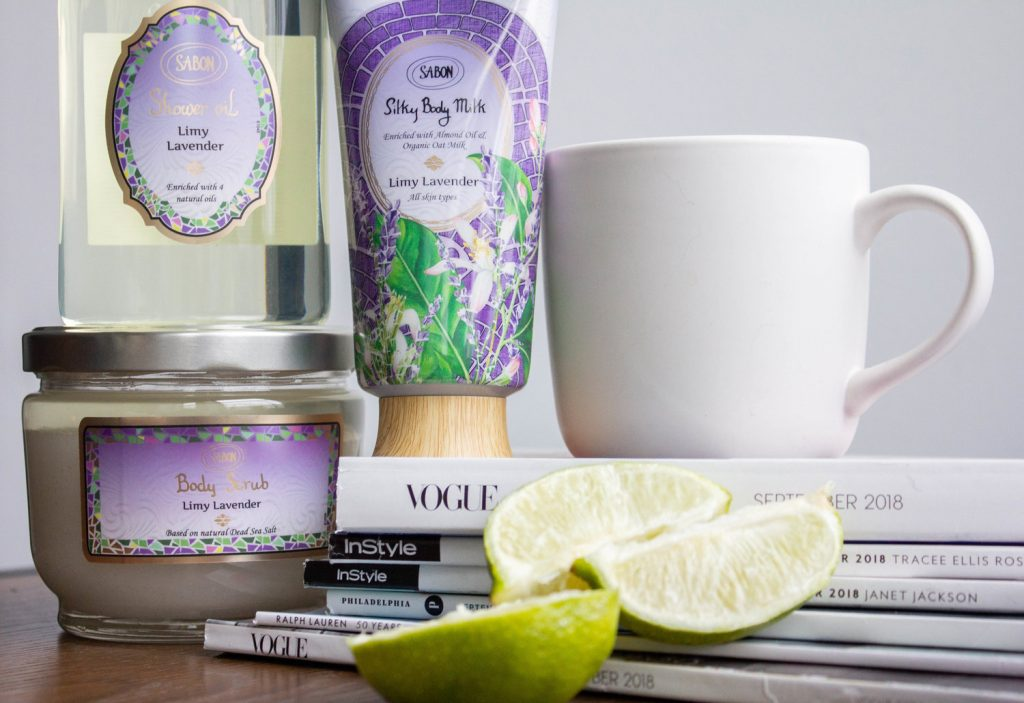 a stack of skincare products from the brand Sabon NYC, next to a coffee mug and slices of lime on a pile of magazines.