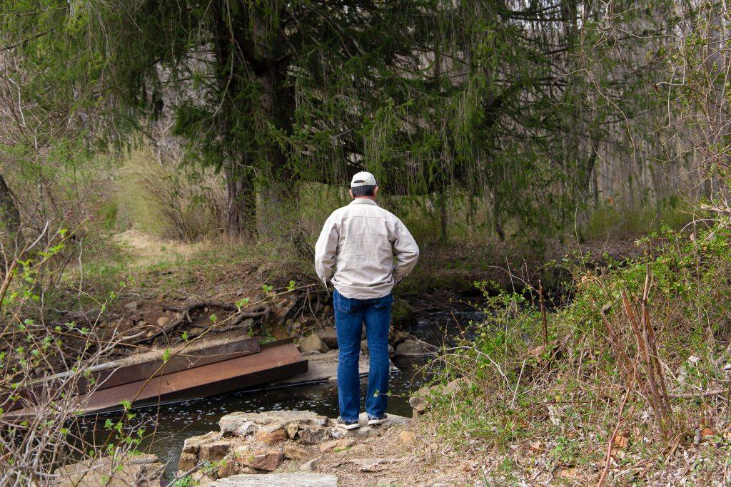 Bianca's father looking into a river on the side of the trail. He is wearing jeans, a tan jacket and a white snapback hat.