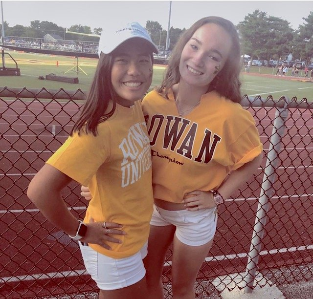 Abby posing with her friend at a football game.