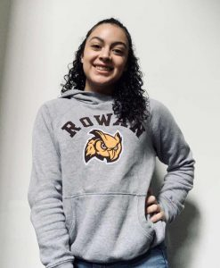 Ariana poses in her Rowan gear against a white wall.