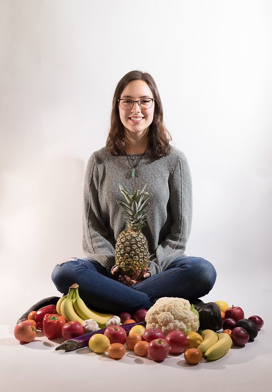 Hannah sits criss cross apple sauce surrounded by colorful fruits and vegetables while holding a pineapple.