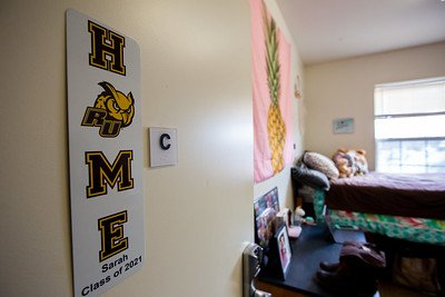 "A Rowan dorm room, focused on the ""Home"" wall hanging with the O as a Rowan owl."
