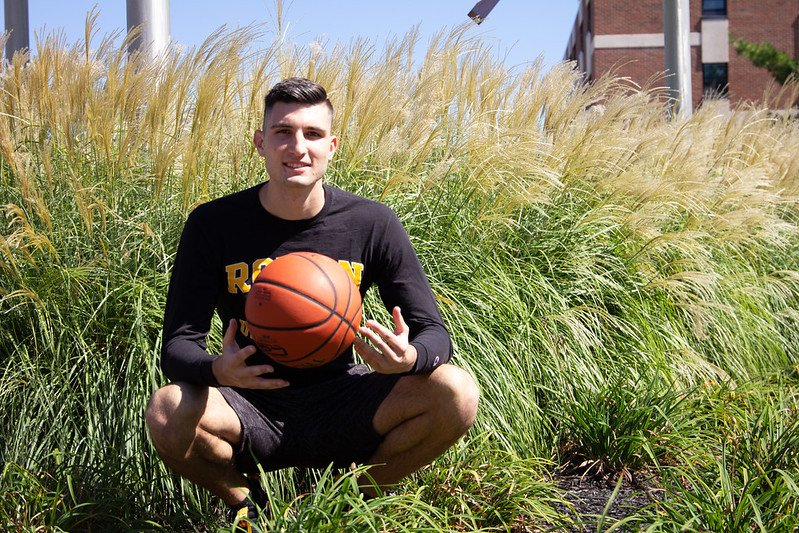 Marko crouches in front of tall grass, holding a basketball.