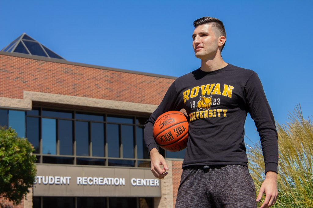 Marko stands holding a basketball, looking to the horizon.