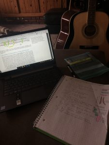 Mia's laptop, a notebook, and guitar.