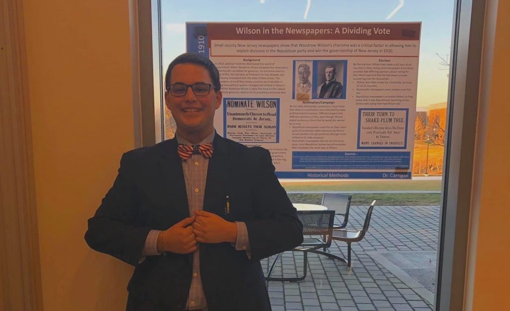 Peter stands clasping his hands in front of his suit, smiling proudly in front of his poster at a poster session.