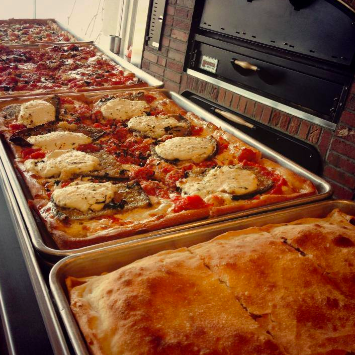 Row of square pizzas coming out of the oven.