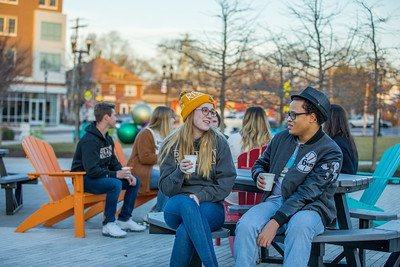 Friends sit and chat in the cold, bundled up with jackets holding coffee.