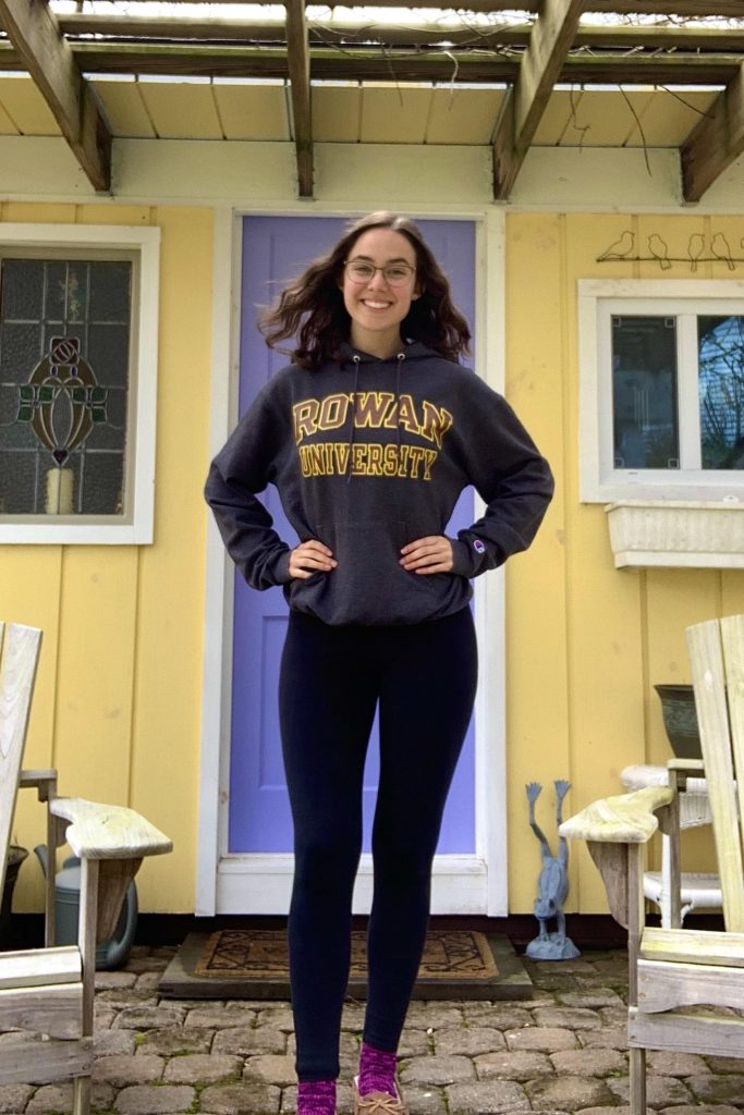 Hannah smiling and posing in front of a yellow shed with a purple door wearing a Rowan University hoodie.