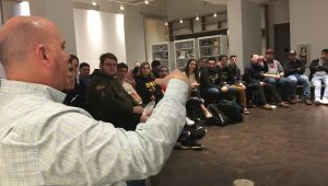 Students listen to a professional in sports communication during a Pizza with the Pros event