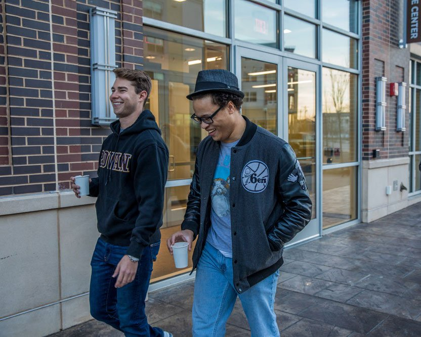 Christian walks with a friend down Rowan Boulevard