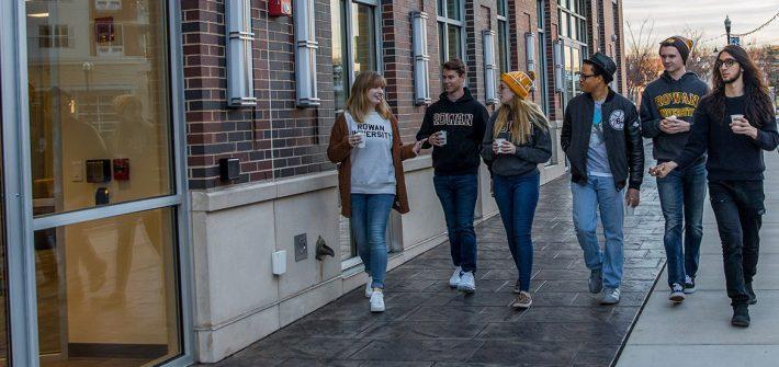 Christian walks with a group of students down Rowan Boulevard