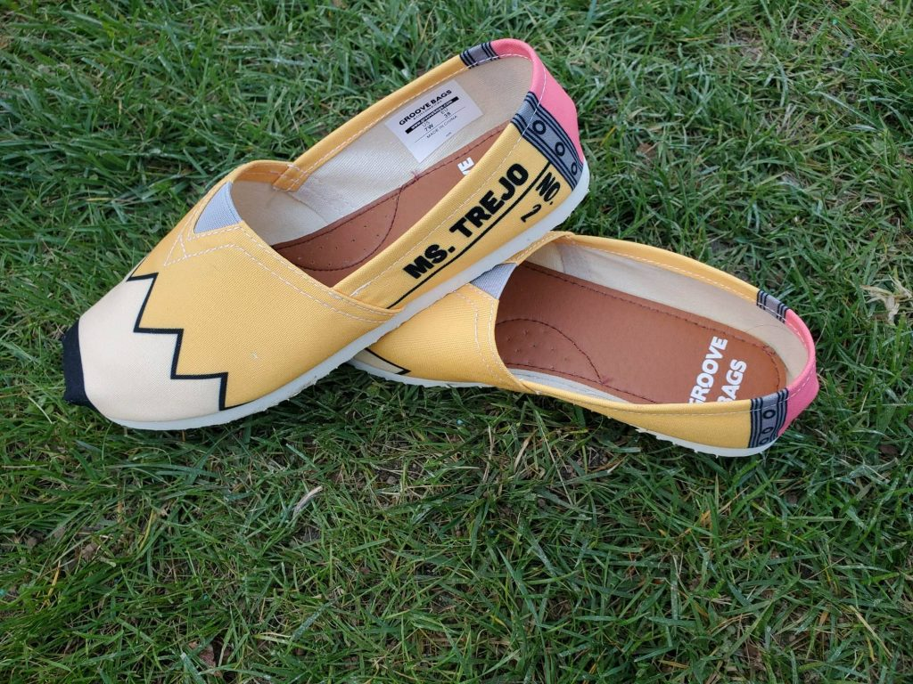 Yellow shoes customized with the word Ms. Trejo.