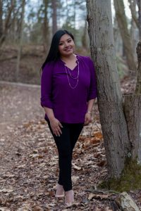 Portrait of Rosalba in woods, standing against a tree.