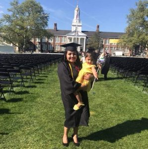 Rosalba stands in her graduation gown holding her daughter, with Bunce Hall in the background.