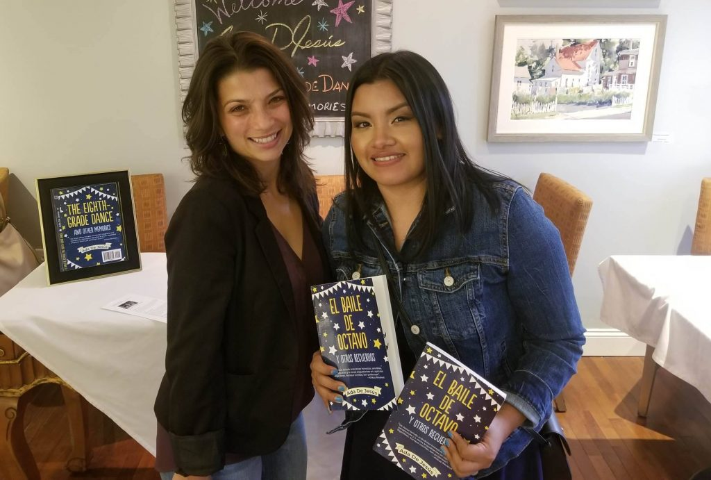 Rosalba stands with her cooperating teacher holding a book.