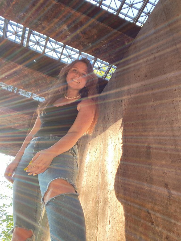 Portrait of Haley Flores looking down with sun casting in the frame