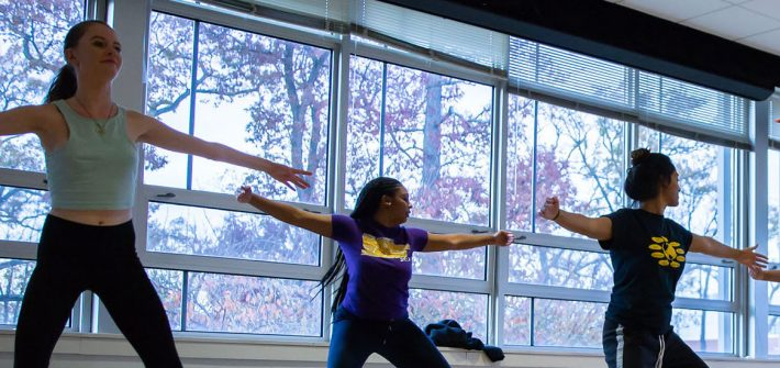 students dancing in a bright room with windows.