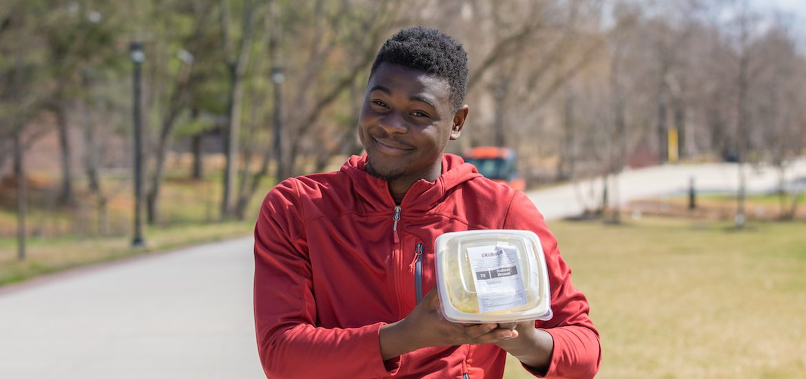 Robert Brown poses with Freshens rice bowl on campus.