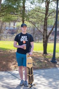Rowan accounting major Rob poses with his skateboard near Mimosa Hall.