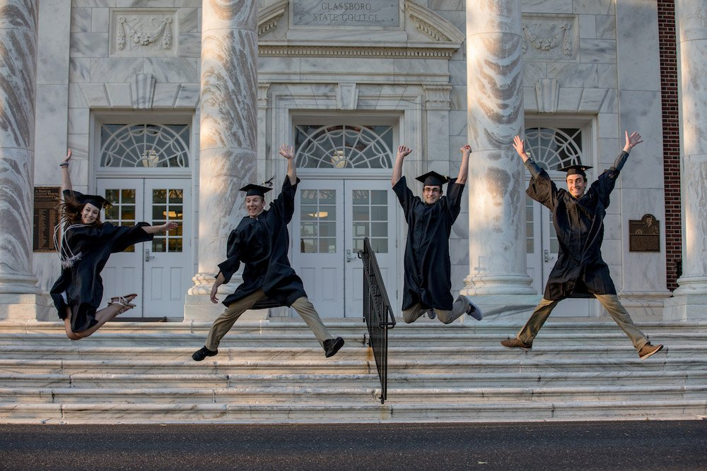 four grads jump in commencement attire.
